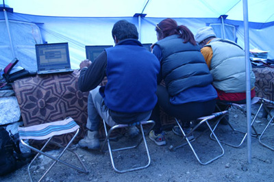Three climbers huddle over the computers checking their hotmail accounts and downloading the weather reports.